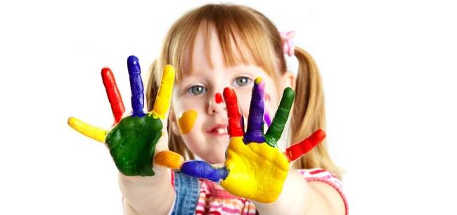 Fetita cu mainile colorate in multiple culori